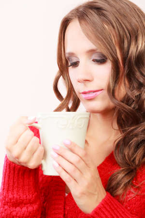 red cardigan: Attractive fall girl long hair red autumnal sweater holding white mug with coffee warm beverage. Woman warming herself Stock Photo