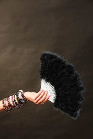 black feather: Party new year celebration and carnival concept. Woman holding black feather fan in hand Stock Photo