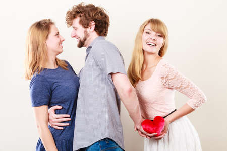 La traición y el concepto de infidelidad. Muchacho hermoso con dos atractivas chicas Blondie. Hombre engaño mujeres por engañar eligen un solo y ofrecen su corazón a otro.