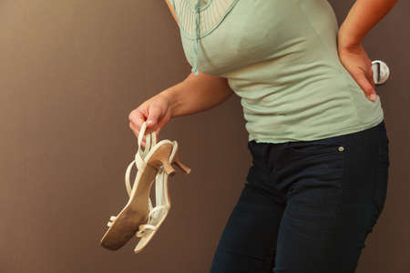 back ache: Aches and pains concept. Sick woman having bad ache and pain health problem. Female with hand on her back holding high heels. Stock Photo
