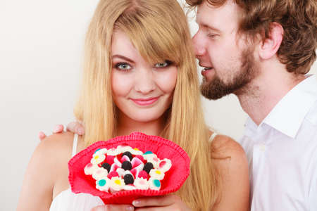 secret love: Loving couple with candy bunch bouquet flowers. Man whispering to woman ear sharing secret. Love and flirt concept. Stock Photo