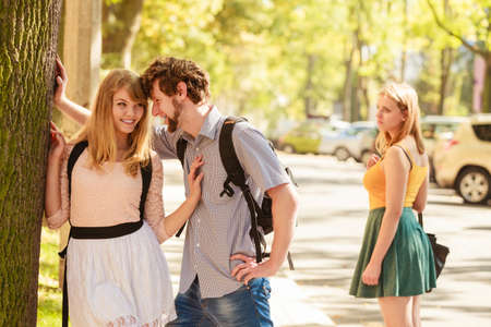 envious: Jealous girl looking at flirting couple outdoor. Happy young woman and man couple dating. Summer romance affair.