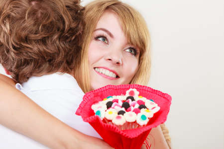 thanking: Loving couple with candy bunch bouquet flowers hugging. Pretty woman thanking man for present gift. Love concept.