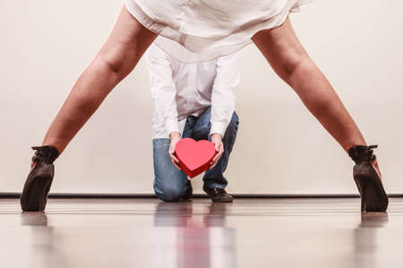 dominant woman: Man guy holding heart shaped present gift box for hot sexy woman girl in high heels. Valentine day love concept.