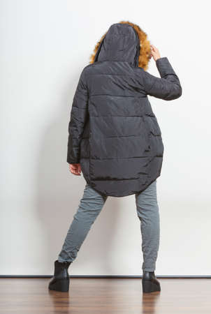 modern girls: Back view of young fashionable girl wearing jacket with hood. Fashion in winter time.