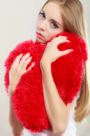 sad heart: Broken heart love concept. Sad unhappy woman hugging red heart pillow closeup Stock Photo