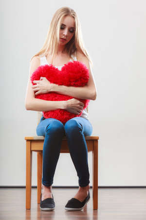 heartbreak issues: Broken heart love concept. Sad unhappy woman sitting on chair hugging red heart pillow
