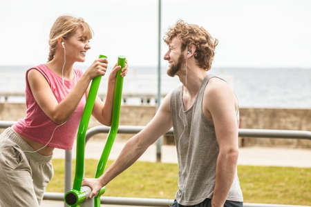 escucha activa: Active woman exercising on elliptical trainer machine and man listening to music. Happy fit sporty girl in training suit working out at outdoor gym. Sport fitness and healthy lifestyle concept.