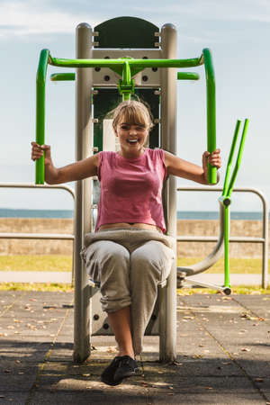 outdoor sport: Active young woman exercising on chest press machine. Strong girl in training suit working out at outdoor gym. Sport fitness and healthy lifestyle concept.