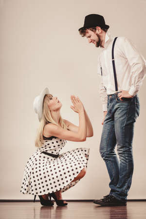 broken trust: Girlriend trying to convince boyfriend. Woman on knees asking begging for forgivness. Conflicted young couple. Relationship problem. Stock Photo
