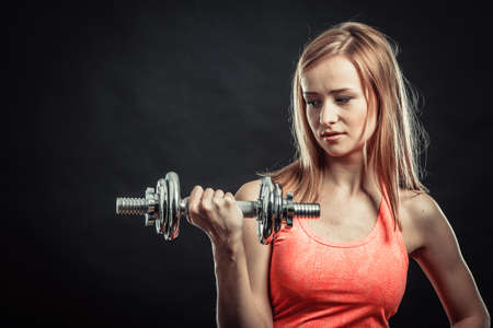 Bodybuilding. Strong fit woman exercising with dumbbells. Muscular blonde girl lifting weights studio shot on black background