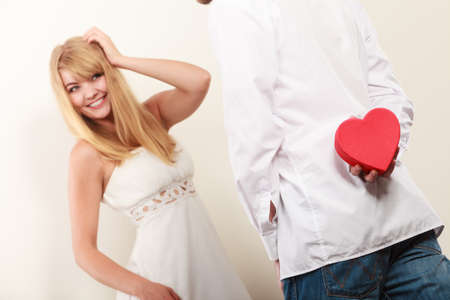 gift behind back: Man holding heart shaped gift box for pretty woman. Guy with surprise present behind back. Valentine day love concept. Stock Photo