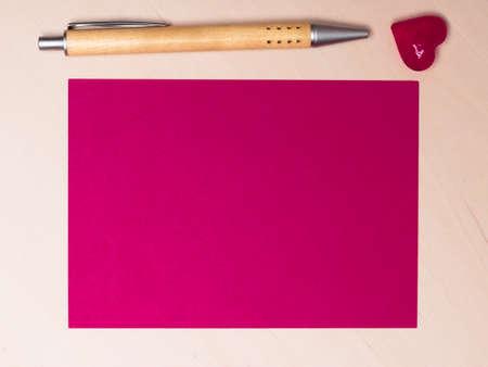 hoja en blanco: hoja en blanco de papel rosa con el símbolo del amor del corazón y el lápiz sobre la superficie de madera. Antecedentes para el Día de San Valentín o de boda.