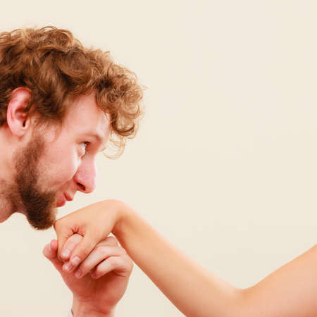a courtesy: Polite man guy kissing woman girl hand. Couple love. Courtesy gesture.