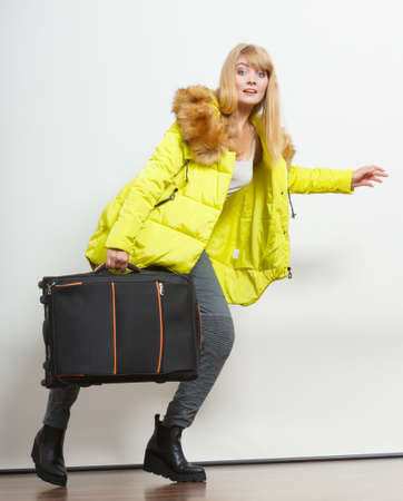 running late: Happy young woman in warm jacket with suitcase running late. Gorgeous blonde tourist travel girl. Tourism.