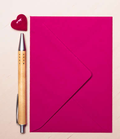 notecard: Pink blank envelope little heart and pen on wooden surface.  Valentine day card, love or wedding greeting concept. Stock Photo