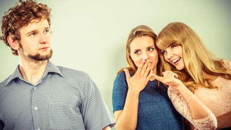 mocking: Young women friends talking gossiping about man. Two women whispering sharing secret news. Stock Photo