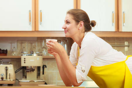 energizing: Pensive mature woman drinking cup of coffee in kitchen. Housewife female with hot energizing beverage. Caffeine energy.