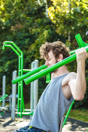 outdoor fitness: Active young man exercising on leg raise. Muscular sporty guy in training suit working out at outdoor gym. Sport fitness and healthy lifestyle concept.