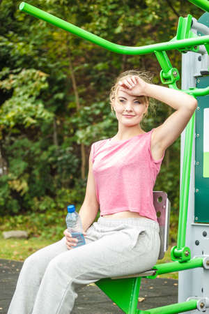 outdoor exercise: Woman with bottle of water relaxing at outdoor gym. Young girl taking break from fitness exercise. Healthy lifestyle.