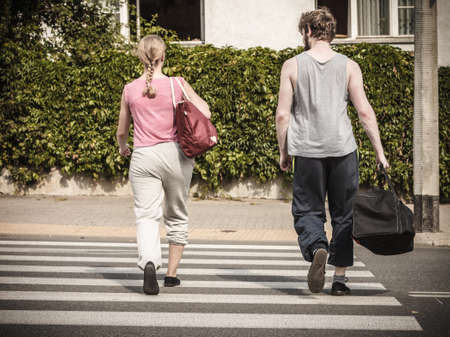 Couple man and woman with sport gym bags crossing pedestrian crosswalk outdoor. Active young girl and guy in training suit sportswear.