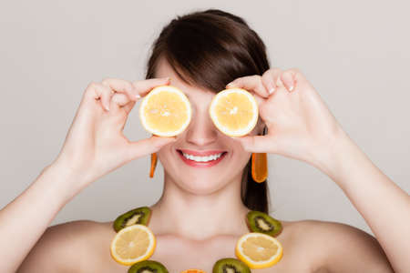 recommending: Diet. Girl with necklace of fresh citrus fruits covering eyes with lemons doing fun on gray. Woman recommending healthy food.