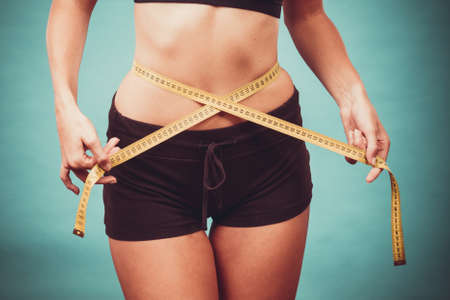 waistline: Weight loss, slim body, healthy lifestyle concept. Fit fitness girl measuring her waistline with measure tape on blue