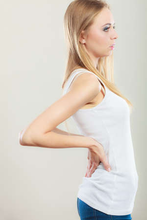 working hours: Long working hours and health. Young female with backache. Woman with back pain on gray Stock Photo