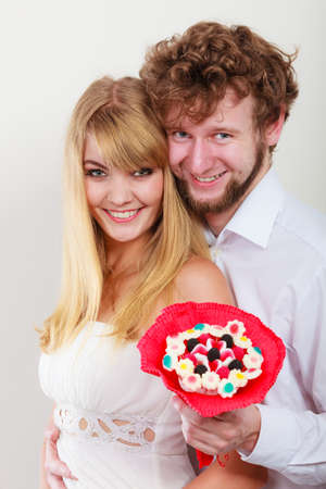 mujer enamorada: Loving couple with candy bunch bouquet flowers. Man and woman holding present gift. Foto de archivo
