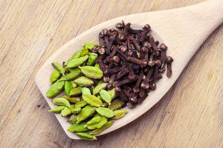 Green cardamom pods and cloves on wooden spoon rustic table background