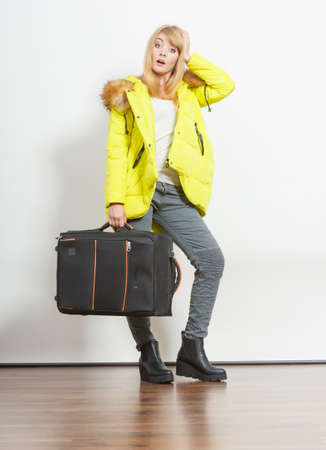 warm jacket: Young woman in warm jacket with suitcase.