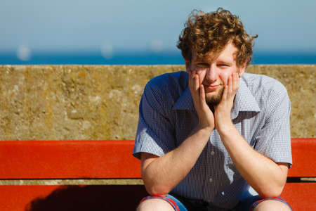 jaded: Tired exhausted man sitting on bench by sea ocean. Young guy relaxing outdoor. Summer vacation. Stock Photo