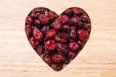 cranberry fruit: Dried cranberries cranberry fruit in shape of heart on wooden surface background