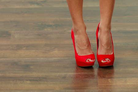 high heeled shoes: Female fashion. Closeup red high heels spiked fashionable shoes on female legs Stock Photo