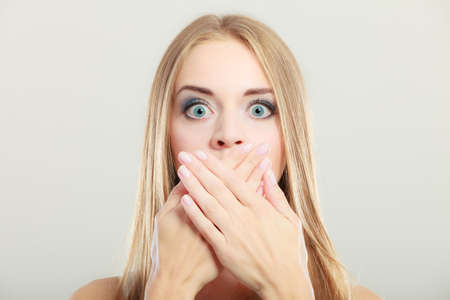 wide eyed: Closeup young amazed woman wide eyed covering her mouth with hands on gray