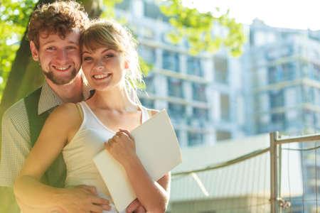 Bienes raíces y el concepto de familia - pareja joven que busca en los planes de construcción de proyectos modelo soñando con nueva casa en la zona residencial moderna, obra en construcción en el fondo