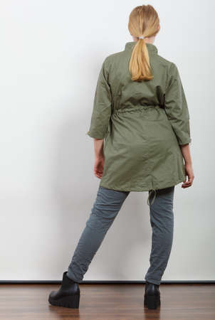 woman back: Woman girl in dark green khaki coat and winter boots posing in studio. Autumn fall fashion.