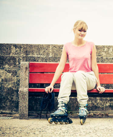 blades: Woman girl with roller skates blades sitting on bench outdoor.