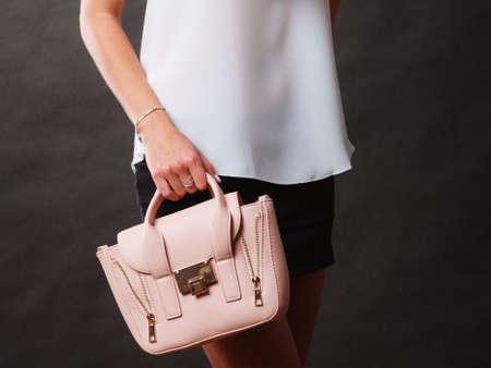 Elegant outfit. Female fashion. Girl in fashionable clothes holding bag handbag on dark