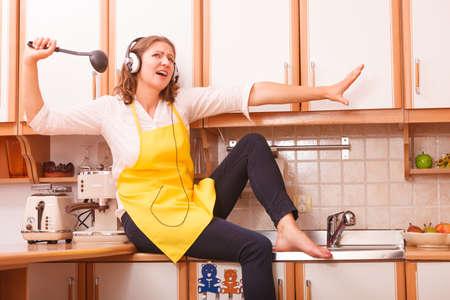 キッチンでリラックスします。歌や踊りの音楽を聞いています。面白い幸せな主婦は、座って、リラックス黄色のエプロンを着て家でイヤホンでシ