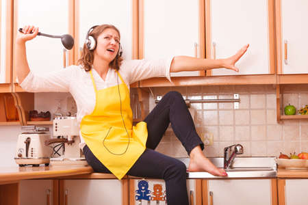 mujer ama de casa: Rel�jese en la cocina. Escuchar el canto de la m�sica y el baile. Feliz divertido del cocinero del cocinero ama de casa con los auriculares que llevan delantal amarillo sentarse y relajarse en casa. Foto de archivo