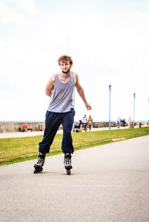 rollerskating: Active young man in training suit rollerskating outdoor. Guy riding enjoying sport.
