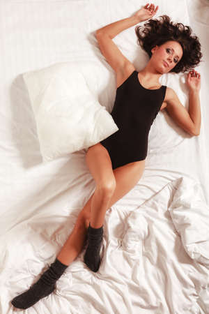 awaking: Young attractive woman relaxing lazing in her bedroom at the morning.