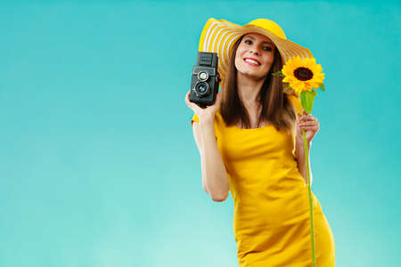 summer woman wearing yellow dress and hat with sunflower and stock