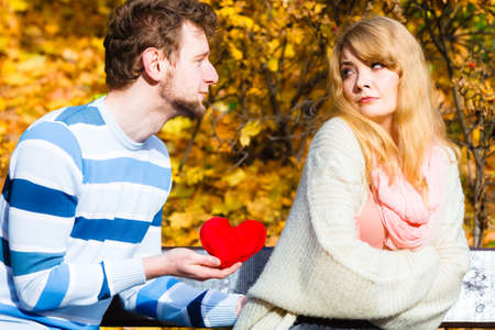 to confess love: Confessing love and affection with romantic gesture. Rejection and disapproval. Negative reaction. Pair sit on bench in park man hold plush heart showing his emotions girl refuse. Stock Photo
