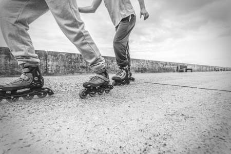 rivals rival rivalry season: Exercising and competition in sport. Healthy lifestyle and wellbeing. Summertime hobby. Young people race together on blades having fun closeup on legs black and white.