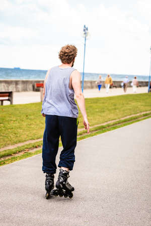 free riding: Outdoors activities sport and hobby. Wellbeing and exercising. Man have fun riding  blades in park spending free time in summer.