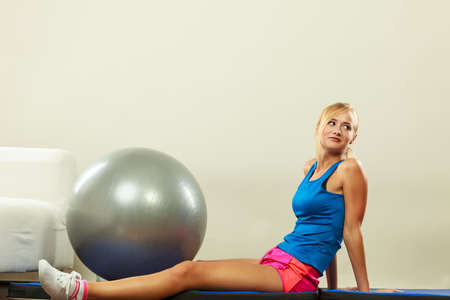 fit ball: Young attractive slim woman in sportswear doing fitness exercises with fit ball at home Stock Photo