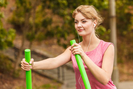 escucha activa: Active woman exercising on elliptical trainer machine listening to music at outdoor gym. Foto de archivo