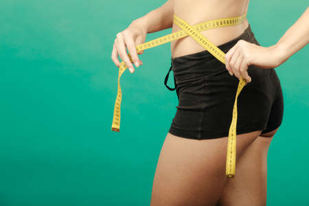waistline: Fit fitness girl measuring her waistline with measure tape on green Stock Photo